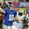 Photo - New York Giants quarterback Eli Manning (10) throws a pass away from New York Jets defensive end Muhammad Wilkerson (96) and Ricky Sapp (55) during the first half of a preseason NFL football game, Saturday, Aug. 24, 2013, in East Rutherford, N.J. (AP Photo/Bill Kostroun)