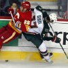 Minnesota Wild\'s Tom Gilbert, right, collides with Calgary Flames\' Steve Begin during the third period of an NHL hockey game in Calgary, Alberta, Saturday, Feb. 23, 2013. (AP Photo/The Canadian Press, Jeff McIntosh)