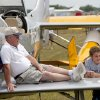 FILE - In this July 27, 2009, file photo, Lanny Rundell of Winnsboro, La. and his grandson Cole Uffman take a rest on their plane at the Experimental Aircraft Association\'s AirVenture in Oshkosh, Wis. One of the nation's largest air shows begins Monday, July 29, 2013, in Wisconsin, and for each of the 10,000 planes flying in, the federal government will collect about $45 for air traffic control services. The fee has angered pilots, who already pay for air traffic control through a fuel tax. (AP Photo/Mike Roemer, File)