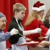 Volunteers in the serving line put food on guests\' plates. From left are Jim Scheihing of Edmond and his son, Dylan, and Hellen Kellar, The Scheihings came as a family, making their first visit to volunteer at the Red Andrews Dinner. Jim and his wife, Kari, were accompanied by their three children, Dylan, Jake and Carly. Kari Scheihing said they would celebrate the Christmas holiday as a family in their home later in the day. It was Kellar\'s first time to volunteer, too. Hundreds were served a traditional Christmas meal at the annual Red Andrews Dinner inside the Cox Convention Center on Christmas Day, Dec. 25, 2012. An army of volunteers showed up despite snow and ice and hazardous driving conditions. They accompanied each guest through the serving line and carried their trays and seated them at their tables. Other volunteers distributed a small mountain of toys and stuffed animals that were donated for the event. Photo by Jim Beckel, The Oklahoman