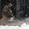 Brad Johnson pushes the heavy snow off the sidewalk in the blowing snow Thursday Dec. 20, 2012 in downtown Burlington, Iowa. (AP Photo/The Hawk Eye, John Gaines)