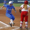 Kentucky\'s Nikki Sagermann (77) celebrates as she score behind La.-Lafayette\'s Lexie Elkins (33) during a Women\'s College World Series game between La.-Lafayette and Kentucky at ASA Hall of Fame Stadium in Oklahoma City Thursday, May 29, 2014. Photo by Bryan Terry, The Oklahoman