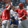 Photo - Los Angeles Angels' Albert Pujols, right, is congratulated by David Freese after hitting a solo home run during the first inning of a spring exhibition baseball game against the Kansas City Royals Thursday, March 20, 2014, in Surprise, Ariz. (AP Photo/Darron Cummings)