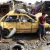 An Iraqi boy stands near a destroyed car at the scene of a car bomb attack in Baghdad\'s northern Kazimyah neighborhood, Friday, Feb. 8, 2013. Car bombs struck two outdoor markets in Shiite areas of Iraq on Friday, killing and wounding scores of people, police said. (AP Photo/ Karim Kadim)
