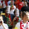Portuguese fans wearing masks of German Chancellor Angela Merkel hold glasses of beer on the stands during the Euro 2012 soccer championship Group B match between Denmark and Portugal in Lviv, Ukraine, Wednesday, June 13, 2012. (AP Photo/Armando Franca)