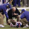 Trainers work on New York Giants safety Antrel Rolle (26) after he was injured during the second half of the NFL Super Bowl XLVI football game against the New England Patriots, Sunday, Feb. 5, 2012, in Indianapolis. (AP Photo/David Duprey) ORG XMIT: SB432
