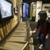 In this photo taken Wednesday, Dec. 26, 2012, Karina Chuquihuaccha, a visitors service representative at the museum, tries out an interactive display on railroads at Seattle\'s Museum of History and Industry, in the city\'s South Lake Union neighborhood.
