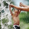 CHILD / CHILDREN / KIDS / WATER ACTIVITIES / HOT WEATHER: Jerrod Williams, Jr., 2, is lifted into the air by his mother as a water-filled bucket is dumped onto him at at a spray park in Douglass Park, NE 10 and Carverdale. Williams and other children enjoyed the cool refreshment of the water at the spray park on the first day of summer, June 21, 2010. Photo by Jim Beckel, The Oklahoman ORG XMIT: KOD