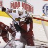 Chicago Blackhawks\' Brandon Saad (20) slams into Phoenix Coyotes goalie Mike Smith, right, during the second period in an NHL hockey game, Friday Feb. 7, 2014, in Glendale, Ariz. (AP Photo/Ross D. Franklin)