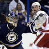 Photo - St. Louis Blues goalie Ryan Miller, left, grabs a puck as Detroit Red Wings' Luke Glendening watches during the third period of an NHL hockey game Sunday, April 13, 2014, in St. Louis. The Red Wings won 3-0. (AP Photo/Jeff Roberson)