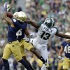 Photo - Notre Dame safety Matthias Farley, left, intercepts a pass intended for Michigan State wide receiver Bennie Fowler (13) during the second half of an NCAA college football game in South Bend, Ind., Saturday, Sept. 21, 2013. Notre Dame defeated Michigan State 17-13. (AP Photo/Michael Conroy)