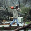 A Hattiesburg, Miss., resident walks through a tornado damaged neighborhood Monday, Feb. 11, 2013, after cutting away branches blocking a senior citizen\'s entrance to her home following a Sunday afternoon tornado that caused damage throughout the South Mississippi college town. (AP Photo/Rogelio V. Solis)