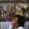 Photo - Rita de Cassia Marciano laughs under her tent decorated with saints from the Afro-Brazilian religion Candomble as she waits for clients in Rio de Janeiro, Brazil, Thursday, June 26, 2014. Candomble was developed by Brazil's slave populations, who associated the gods of the Yoruba people of West Africa with the pantheon of Roman Catholic saints in a bid to perpetuate their beliefs in the New World. (AP Photo/Leo Correa)