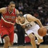 Photo - San Antonio Spurs guard Manu Ginobili, right, of Argentina, drives around Portland Trailblazers forward Nicolas Batum during the first half of an NBA basketball game on Wednesday, March 12, 2014, in San Antonio. (AP Photo/Darren Abate)