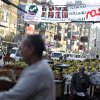 An Egyptian fruit vendor waits for customers under a banner with Arabic writing that reads,