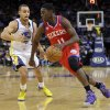 Philadelphia 76ers\' Jrue Holiday (11) dribbles past Golden State Warriors\' Stephen Curry (30) during the first half of an NBA basketball game in Oakland, Calif., Friday, Dec. 28, 2012. (AP Photo/Marcio Jose Sanchez)