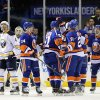 Photo - New York Islanders' Frans Nielsen (51) is congratulated by teammates as Buffalo Sabres' Jamie McBain (4) after Nielsen scored in the first period of an NHL hockey game on Saturday, March 15, 2014, in Uniondale, N.Y. (AP Photo/Kathy Kmonicek)