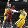 Photo -   Miami Heat forward LeBron James, center, is tied up as he drives the lane for a shot by Denver Nuggets center Kosta Koufos, left, and forward Andre Iguodala in the first quarter of an NBA basketball game in Denver on Thursday, Nov. 15, 2012. (AP Photo/David Zalubowski)