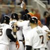 Photo - Miami Marlins players surround Giancarlo Stanton at the plate after he hit a grand slam to defeat the Seattle Mariners 8-4 during the ninth inning of an interleague baseball game on Friday, April 18, 2014, in Miami. (AP Photo/Lynne Sladky)