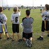 Assistant Coach Mike Krase gets on his players\' level to watch a play during a flag football game at Mitch Park in Edmond on Tuesday, Sept. 9, 2008. By John Clanton, The Oklahoman