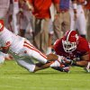 Clemson\'s Tajh Boyd (10) stretches in the grip of North Carolina States Robert Caldwell (48) during the first half of an NCAA college football game in Raleigh, N.C., Thursday, Sept. 19, 2013. (AP Photo/Karl B DeBlaker)