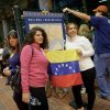 Mailyn Yoria, 19, and her mother Yelby Yoria of Miami, smile as they pose for a picture holding a Venezuelan flag as they wait in line to vote at the New Orleans Ernest Morial Convention Center, in New Orleans, Sunday, Oct. 7, 2012. Hundreds of Venezuelans living in the U.S. streamed into New Orleans on Sunday to cast ballots in the presidential election in their homeland, many of them determined to end the 13-year reign of Hugo Chavez. With the country\'s consulate in Miami closed, thousands of Venezuelans traveled by bus, car and plane to cast their votes at the consulate in New Orleans. (AP Photo/Matthew Hinton)