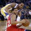 Photo - Philadelphia 76ers' Evan Turner (12) looks to pass after picking up up a loose ball next to Golden State Warriors' Andre Iguodala during the first half of an NBA basketball game, Monday, Feb. 10, 2014, in Oakland, Calif. (AP Photo/Marcio Jose Sanchez)