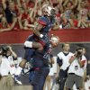 Photo - Arizona's Daniel Jenkins (3) is lifted into the air by teammate Cayman Bundage (61) after scoring a touchdown against Northern Arizona during the first half of an NCAA college football game at Arizona Stadium in Tucson, Ariz., Friday, Aug. 30, 2013. (AP Photo/Wily Low)