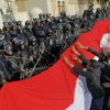 Egyptian protesters hang a giant banner in the colors of Egypt\'s national flag on barbed wires in front of anti-riot soldiers at the entrance to the presidential palace in Cairo, Egypt, Friday, Jan. 25, 2013. Two years after Egypt\'s revolution began, the country\'s schism was on display Friday as the mainly liberal and secular opposition held rallies saying the goals of the pro-democracy uprising have not been met and denouncing Islamist President Mohammed Morsi. (AP Photo/Amr Nabil) ORG XMIT: AMR108