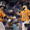 Photo - Houston Astros starting pitcher Dallas Keuchel (60) shakes hands with catcher Carlos Corporan after throwing a complete game against the Seattle Mariners in a baseball game Sunday, May 25, 2014, in Seattle. The Astros won 4-1. (AP Photo/Elaine Thompson)