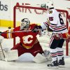 Chicago Blackhawks\' Andrew Shaw, center, swats the puck past Calgary Flames goalie Miikka Kiprusoff, from Finland, during first-period NHL hockey game action in Calgary, Alberta, Saturday, Feb. 2, 2013. (AP Photo/The Canadian Press, Jeff McIntosh)