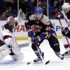 Photo - New York Islanders' Matt Moulson, center, maneuvers the puck between the New Jersey Devils goalie Johan Hedberg, left, and Bryce Salvador during the second period of the NHL hockey game on Sunday, Feb. 3, 2013, in Uniondale, N.Y. (AP Photo/Seth Wenig)
