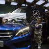 Photo - In this photo taken Sunday, April 20, 2014, a child touches the latest model from Mercedes at an auto show in Beijing, China. Chinese regulators have launched a series of anti-monopoly investigations of foreign automakers and technology providers, stepping up pressure on foreign companies that feel increasingly unwelcome in China. On Wednesday, a regulator said Chrysler and Germany's Audi will be punished for violating anti-monopoly rules. Mercedes Benz and Japanese companies also are under scrutiny. (AP Photo/Ng Han Guan)