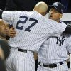New York Yankees\' Alex Rodriguez, right, hugs Raul Ibanez (27) as Derek Jeter watches at left after Ibanez pinch-hit a home run in place of Rodriguez during the ninth inning of Game 3 of their American League division baseball series against the Baltimore Orioles, Wednesday, Oct. 10, 2012, in New York. The Yankees won 3-2. (AP Photo/Bill Kostroun)