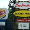 Photo -  A Burger King sign and a Tim Hortons sign are displayed Monday in Ottawa, Ontario. Burger King is in talks to buy Tim Hortons in hopes of creating a new, publicly traded company with its headquarters in Canada. AP Photo   Sean Kilpatrick -