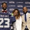 Photo - Seattle Seahawks' Marcus Trufant, left, holds up a team jersey as he stands with his wife Jessica and brothers Isaiah, second right, and Desmond to start a news conference announcing his retirement from football after signing with the team a day earlier, Thursday, April 24, 2014, in Renton, Wash. Trufant started 125 games in a Seattle career that lasted from 2003 to 2012. The cornerback was a first-round pick in 2003 out of Washington State and immediately moved into the starting lineup, playing a key role on the 2005 team that advanced to the franchise's first Super Bowl. (AP Photo/Elaine Thompson)