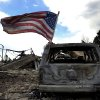 Photo -   A United States flag flies on a burnt car as residents were allowed back on Sunday, July 1, 2012, into the Mountain Shadows subdivision of Colorado Springs, Colo., to visit their homes after the Waldo Canyon fire ravaged the neighborhood. So far, the blaze, now 45 percent contained, has damaged or destroyed nearly 350 homes. (AP Photo/The Denver Post, Helen H. Richardson) MAGS OUT; TV OUT; INTERNET OUT