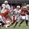 Nebraska quarterback Taylor Martinez (3) runs between Wisconsin\'s Dezmen Southward (12) and Shelton Johnson (24) during the first half of the Big Ten championship NCAA college football game Saturday, Dec. 1, 2012, in Indianapolis. (AP Photo/Michael Conroy)