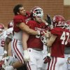 Oklahoma\'s Trey Millard, left, jokes around with lineman Gabe Ikard, center, during spring practice for the NCAA college football team in Norman, Okla., Tuesday, March 12, 2013. Eric Hosek is at right. (AP Photo/Sue Ogrocki) ORG XMIT: OKSO104