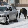 A man loses his balance after he and two companions helped push this car out of snow on a downtown street. A severe winter storm created whiteout conditions and caused snow drifts that made problems for the few motorists who ventured out Tuesday afternoon, Feb. 1, 2011. Photo by Jim Beckel, The Oklahoman