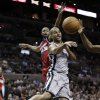 Photo - San Antonio Spurs' Tony Parker, right, of France, passes the ball as Washington Wizards' A.J. Price (12) tries to defend him from behind during the first half of an NBA basketball game, Saturday, Feb. 2, 2013, in San Antonio. (AP Photo/Eric Gay)