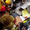 In this photo provided by Miami-Dade Fire Rescue, emergency workers remove an injured man from the rubble after a section of a parking garage under construction at a Miami-Dade College campus collapsed Wednesday, Oct. 10, 2012 in Doral, Fla., killing one worker and trapping at least two others in the rubble, officials said. (AP Photo/Miami-Dade Fire Rescue)