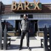 "Photo - FILE - In this April 16, 2014, file photo, actor Ty Burrell, who plays bumbling dad Phil Dunphy on ABC's ""Modern Family,"" stands outside Bar X, the cocktail bar he co-owns, in Salt Lake City. Burrell's support for gay marriage extends beyond the scripted show, as evidenced in December when he served as the official witness to an unplanned lesbian wedding at his bar in Salt Lake City when same-sex marriage was briefly legal in Utah. On Thursday, he'll once again display his support for making gay and lesbian weddings legal when he headlines a fundraiser in Salt Lake City. (AP Photo/Rick Bowmer, File)"