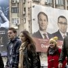 CORRECTS DATE TO DEC. 5 People walk past, backdropped by a large electoral poster of the ruling Social Liberal Union, right, and a movie poster, left, in Bucharest, Romania, Wednesday, Dec. 5, 2012. Romania will hold parliamentary elections on Dec. 9, 2012. (AP Photo/Vadim Ghirda)