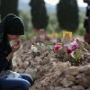 Photo - A woman prays at the grave of Ibrahim Duman, 26, a victim of the mine accident, in Soma, Turkey, Thursday, May 15, 2014. An explosion and fire at a coal mine in Soma, some 250 kilometers (155 miles) south of Istanbul, killed hundreds of workers, authorities said, in one of the worst mining disasters in Turkish history. (AP Photo/Emrah Gurel)