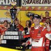 Photo - Kevin Harvick poses with the trophy in Victory Lane after winning the NASCAR Sprint Cup series auto race at Darlington Raceway in Darlington, S.C., Saturday, April 12, 2014. (AP Photo/Mike McCarn)