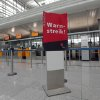 Empty counters and a poster that reads \' Warning Strike\' is seen during a warning strike of employees of the German airliner Lufthansa at the airport in Munich, southern Germany, Monday, April 22, 2013. (AP Photo/Matthias Schrader)