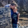 Tracy Streeper hugs five year-old grandson Jesse, as they stand on the north side of Streeper\'s destroyed home. The Streepers had lived in this house for one year. Residents in Luther were allowed to return to the their homes early Saturday, Aug. 4, 2012, after they fled a rapidly moving wildfire yesterday that consumed at least seven structures on South Dogwood Street, leaving smoldering ashes where family homes once stood. Photo by Jim Beckel, The Oklahoman.