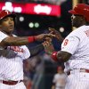 Photo - Philadelphia Phillies' Marlon Byrd, left, celebrates scoring the run along with Ryan Howard, right, on the double by Cody Asche during the fourth inning of a baseball game against the Cincinnati Reds, Saturday, May 17, 2014, in Philadelphia. (AP Photo/Chris Szagola)