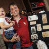 Former OU cheerleader Chris Knute Kochendorfer holds his daughter Jemma Kochendorfer, one-and-a-half, as he poses for a picture with memorabilia of his great grandfather, legendary Notre Dame football coach Knute Rockne, at Kochendorfer\'s home in Oklahoma City, Wednesday, Oct. 24, 2012. Photo by Nate Billings, The Oklahoman